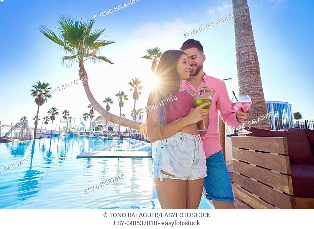 Young couple drinking cocktail in a resort pool in summer vacation
