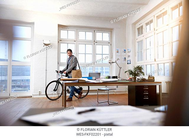 Man with bicycle in a modern informal office