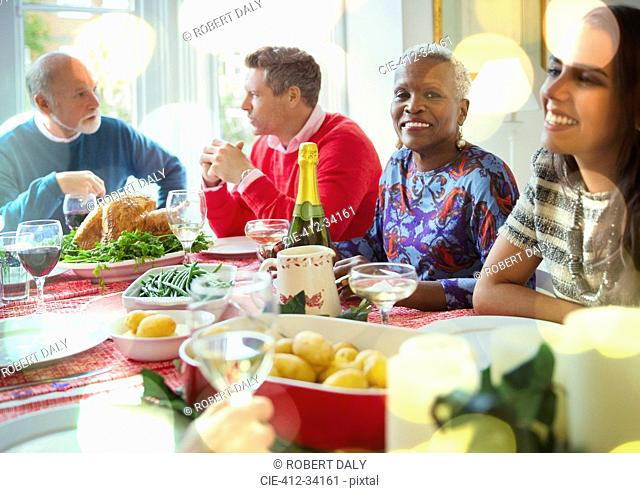 Portrait smiling senior woman enjoying Christmas dinner with family at table