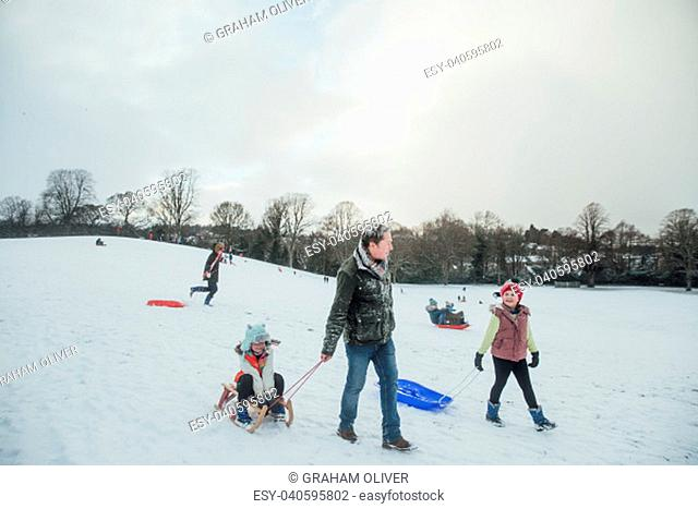 Man is out sledding in the snow with his daughters