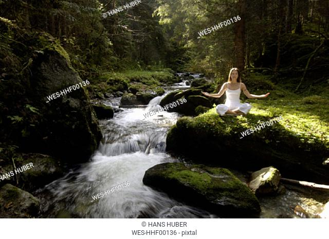 Woman meditating in forest by stream