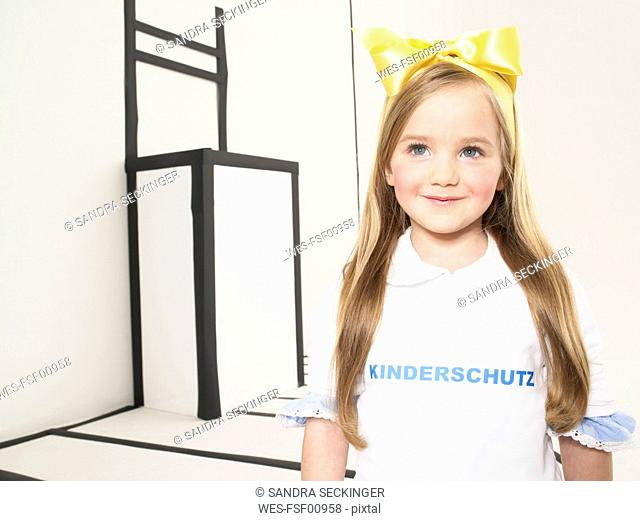 Portrait of smiling little girl dressed up as Alice in Wonderland
