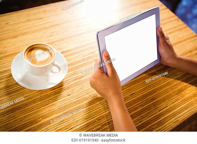 A businesswoman using a tablet and enjoying a coffee