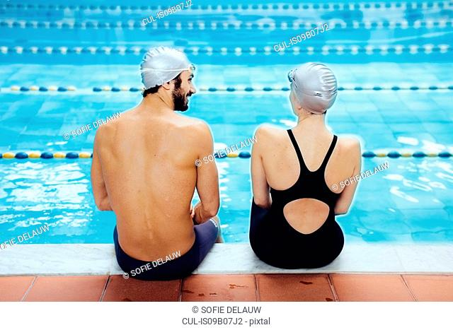 Rear view of couple sitting on poolside