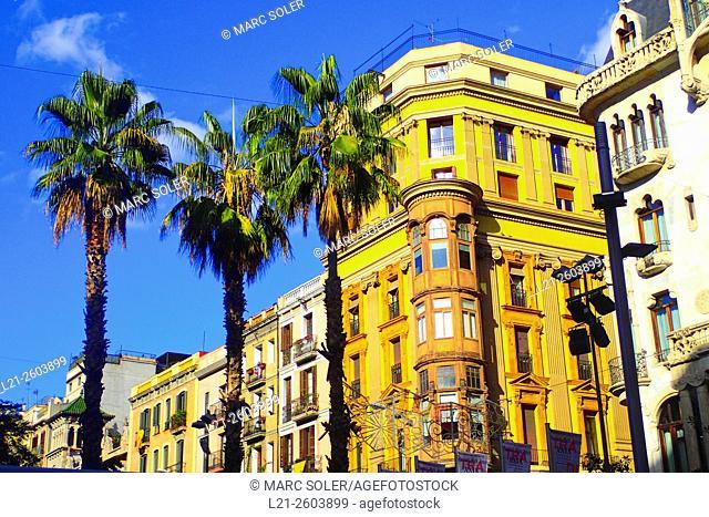 Buildings, palm trees, blue sky. Gracia quarter, Barcelona, Catalonia, Spain