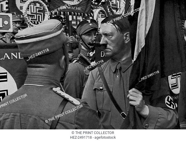 Adolf Hitler dedicating standards at the Nuremberg Rally, Germany, 1935. Hitler (1889-1945) at the 7th Nazi Party Congress. A print from Adolf Hitler