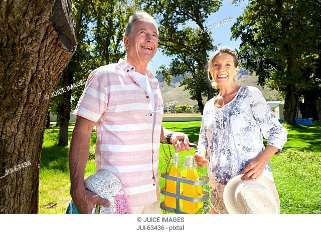Senior couple with picnic bottles in countryside smiling at camera