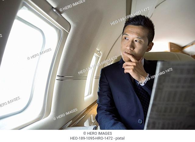 Pensive businessman reading newspaper on corporate jet