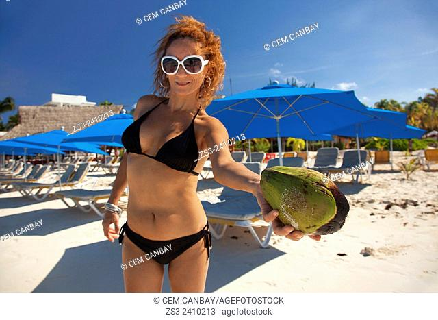 Woman holding a coco nut on the beach, Isla Mujeres, Cancun, Quintana Roo, Yucatan Province, Mexico, Central America