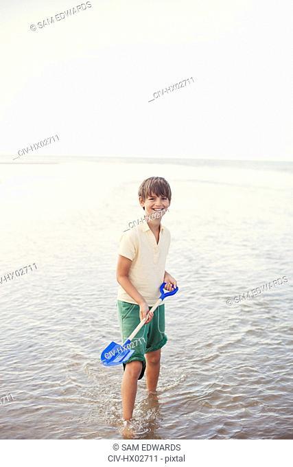 Portrait smiling boy with shovel in ocean surf on summer beach