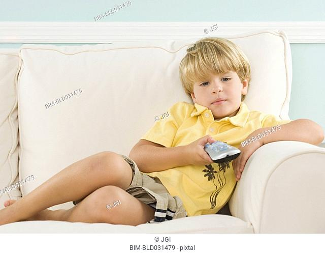 Young boy on sofa pointing remote control