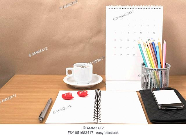 office desk: coffee with phone, wallet, calendar, heart, color pencil box, notepad on wood background