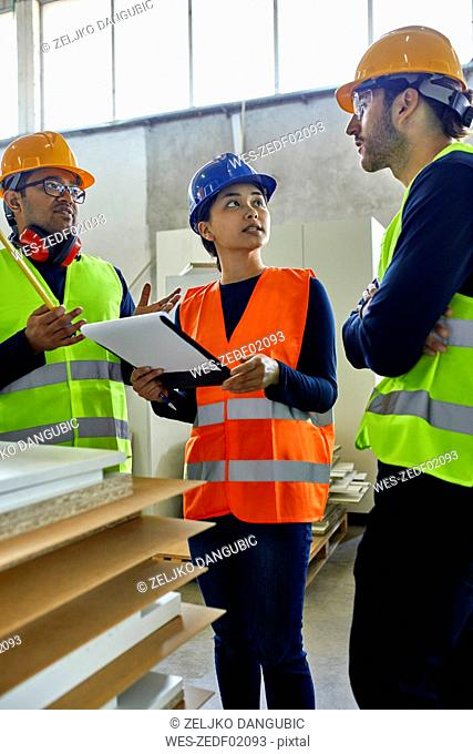 Two men and woman in reflective vests discussing in factory