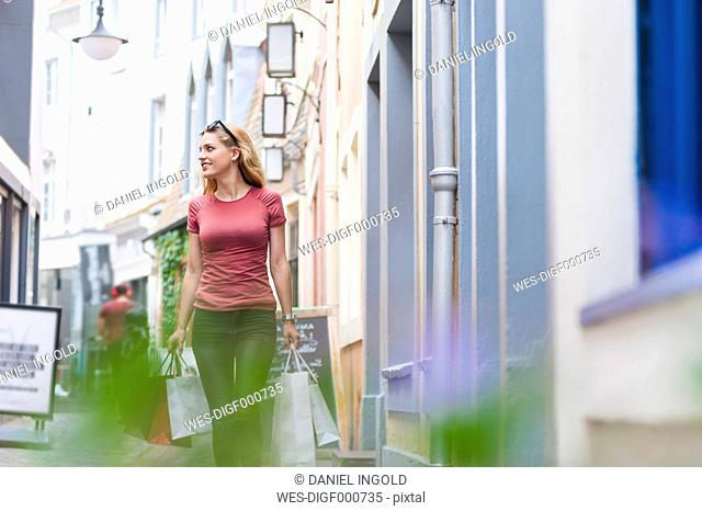 Smiling woman walking on the street carrying shopping bags