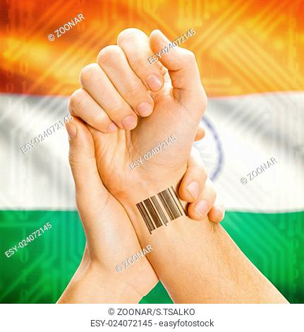 Barcode ID number on wrist and national flag on background - India