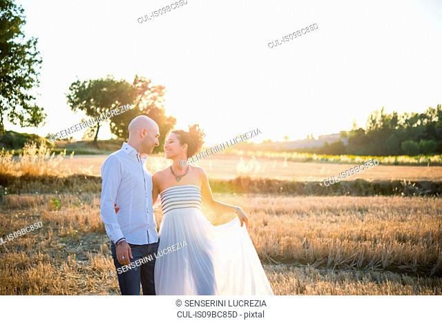 Heterosexual couple standing in field, face to face, smiling