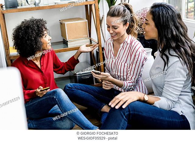 Three happy women sitting on the floor at home with cell phones