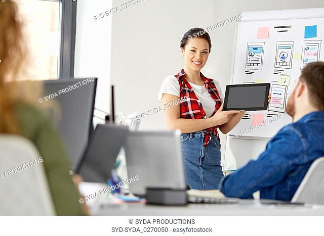 woman showing tablet pc to creative team at office