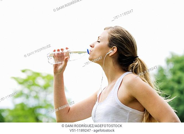 Blonde woman jogging in the park and drinking water