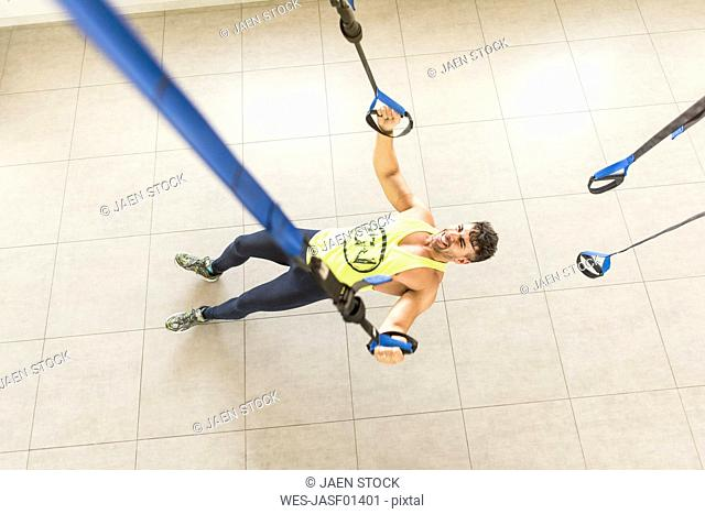 Man doing suspension training in gym
