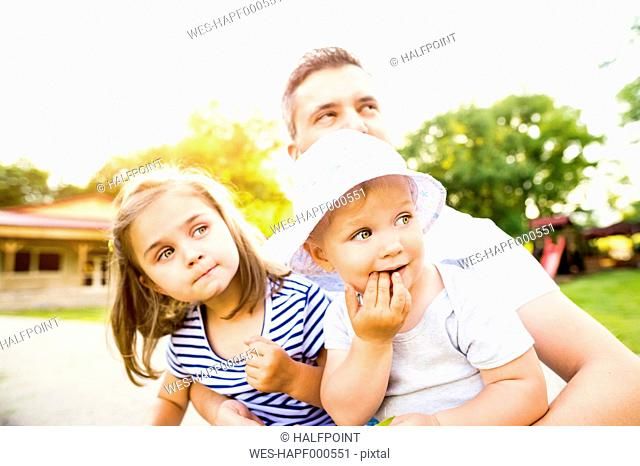 Father and his little daughters watching something in a park