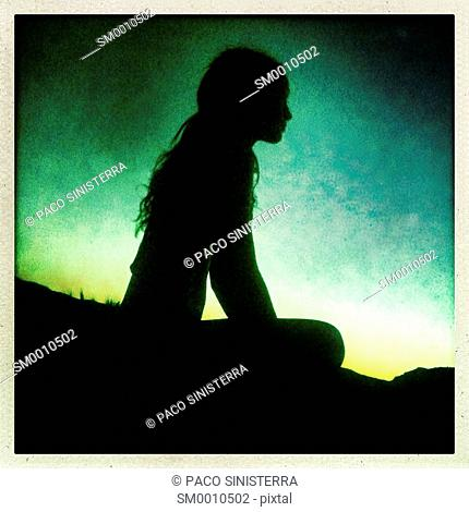 Silhouette of girl looking out to sea in Ibiza, Balearic Islands, Spain