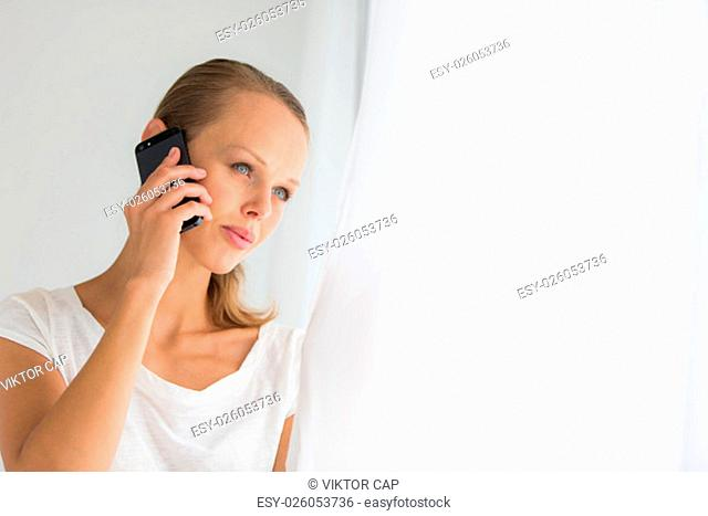 Pretty, young woman calling on her call phone, pensive, concentrating, wearing bright clothes inside a modern, fresh interior (color toned image; shallow DOF)
