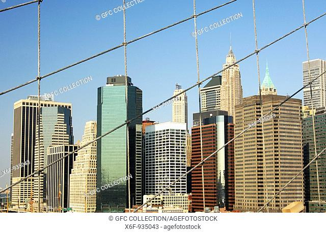 View through the tension ropes of the Brooklyn Bridge across the East River at skyscrapers at the FDR Drive, Financial District, Manhattan, New York, USA