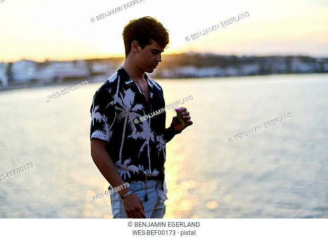 Greece, Crete, Hersonissos, young man holding flower blossom in hand at seaside during sunset