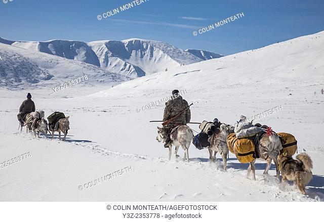 Tsataan ride reindeer towards the Hunkher mountains, spring reindeer round-up, northern Mongolia