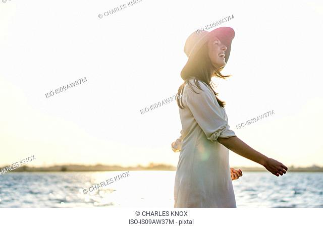 Young woman with hat by sea at sunset
