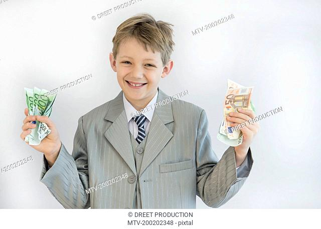 Boy holding paper money in his hand, smiling, portrait