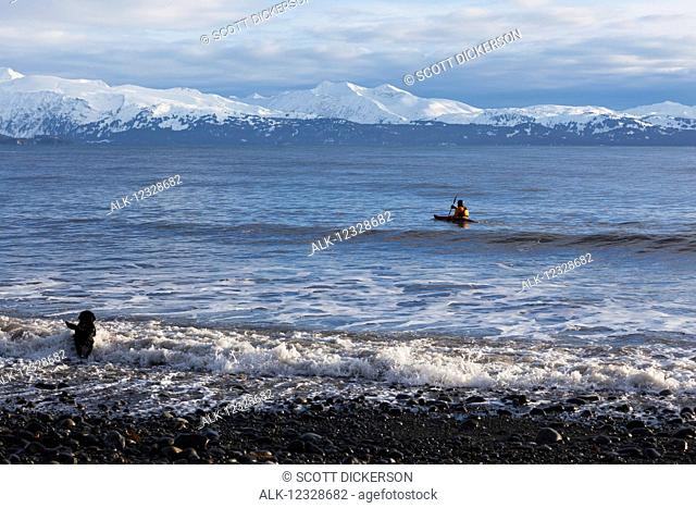 Sea kayaking in Kachemak Bay with a dog running in the water along the shore, South-central Alaska; Homer, Alaska, United States of America