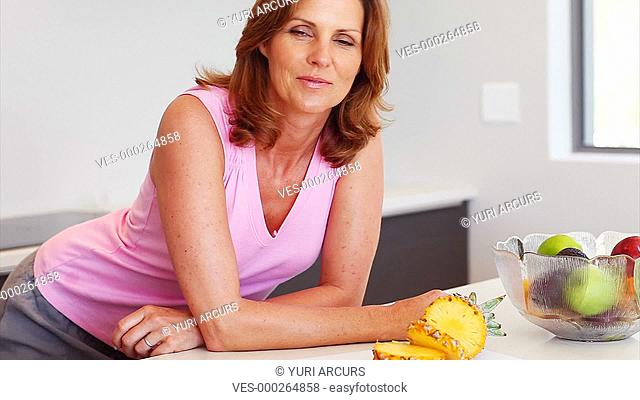 Pretty woman relaxes in her kitchen then decides to have a apple
