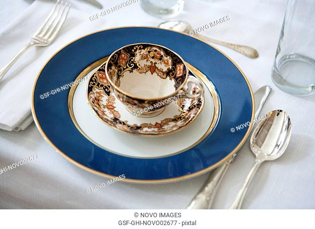 Formal Dining Table Setting with Blue-Accented Teacup and Saucer on Plate with Silverware