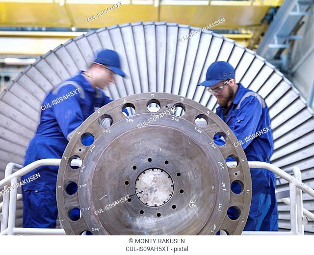 Engineers repairing steam turbine in workshop
