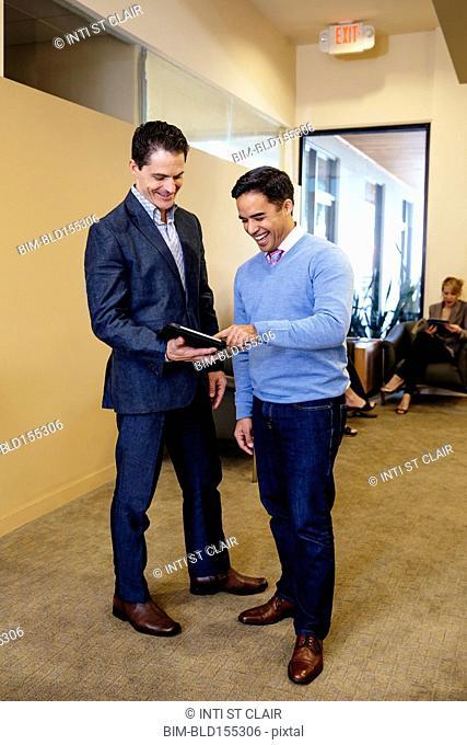 Businessmen using digital tablet in office hallway