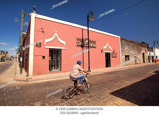 Street scene from the town center with a man riding on a bike in the foreground, Valladolid, Yucatan Province, Mexico, Central America