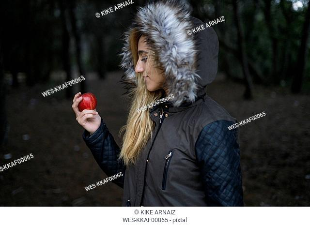 Young woman with red apple wearing hooded jacket