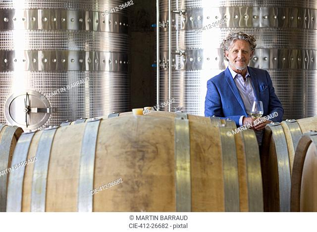 Portrait confident vintner in winery cellar