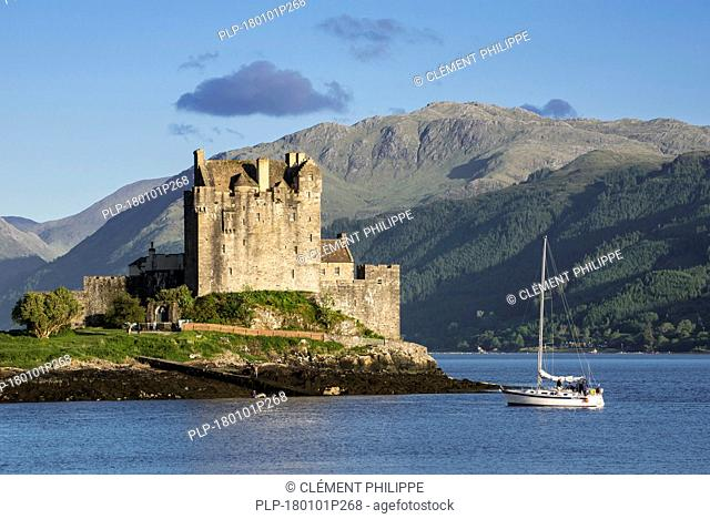 Sailing boat in front of Eilean Donan Castle in Loch Duich, Ross and Cromarty, Scottish Highlands, Scotland, UK