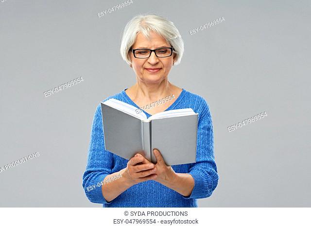 senior woman in glasses reading book