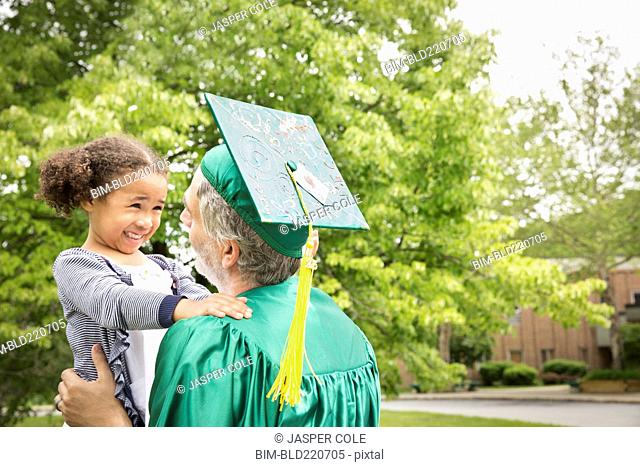 College graduate father hugging daughter