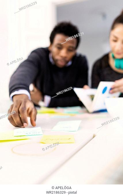 Young businessman reaching for adhesive note while sitting by colleague in office