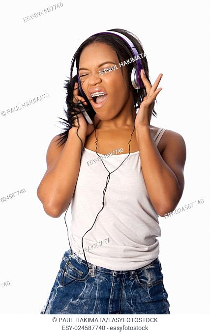 Beautiful teenager happily singing along jamming while listening to music, on white