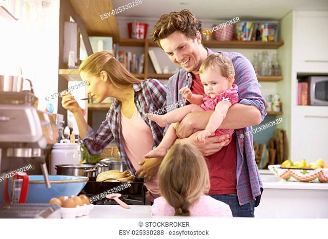 Family Cooking Meal In Kitchen Together