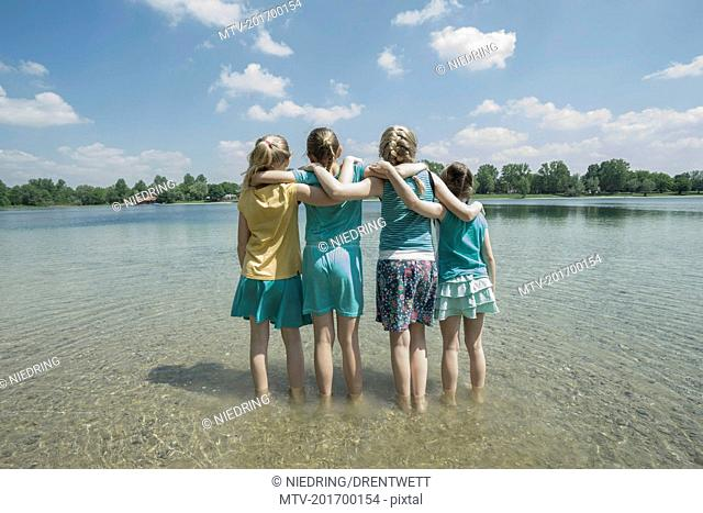 Group of friends standing in the lake, Bavaria, Germany