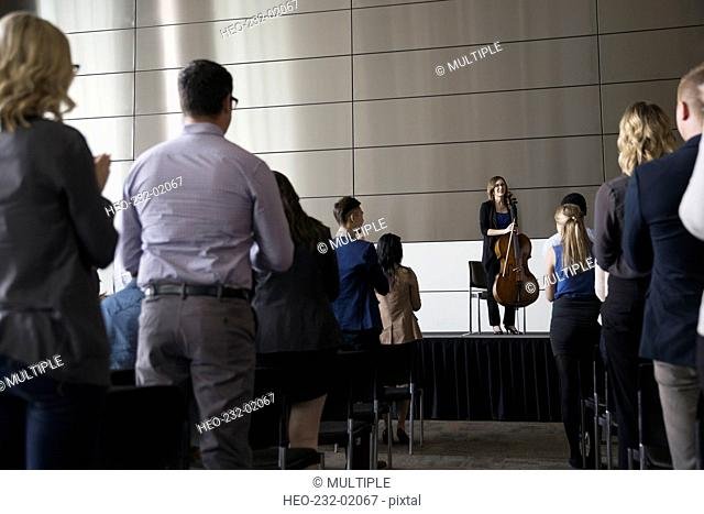 Audience standing ovation to female cellist on stage
