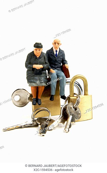 Miniature figurines of elderly couple sitting on padlocks