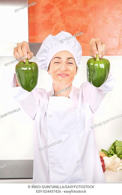 portrait of brunette happy chef woman with professional jacket and hat in white and orange kitchen with two raw fresh big green peppers in her hands